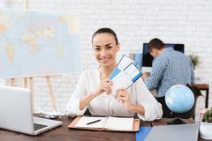 The travel agent keeps tickets for the plane in the travel agency. She offers them to clients. She smiles. On the table she has a toy plane, a laptop Stock Photo