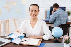The travel agent keeps tickets for the plane in the travel agency. She offers them to clients. She smiles. On the table she has a toy plane, a laptop royalty free stock photo