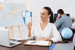 The travel agent keeps tickets for the plane in the travel agency. She offers them to clients. She smiles. On the table she has a toy plane, a laptop Royalty Free Stock Photos