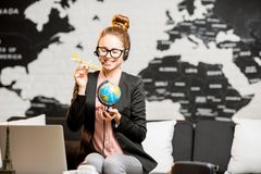 Travel agent portrait on the world map background. Portrait of a female travel agent in suit and headset playing with globe and airplane on the world map Royalty Free Stock Photos