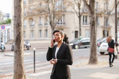 Travel administrator advising tours on smartphone in park. Travel agent talking on smartphone with client and advising cheap tours in park. Pretty female person Royalty Free Stock Photography