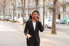 Travel administrator advising tours on smartphone in park. Travel agent talking on smartphone with client and advising cheap tours in park. Pretty female person Stock Image