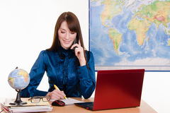 Travel agent writes in a notebook on the phone Stock Image