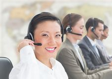 Travel agents with headsets against blurry map. Digital composite of Travel agents with headsets against blurry map Stock Photography