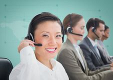 Travel agents with headsets against green map Royalty Free Stock Photos