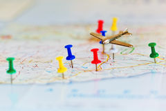 Travel by air concept. Tiny aircraft over the close up captured map with colored pins - trip highlights concept. Macro capture with lens blur focus Stock Image