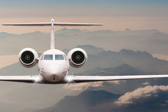 Travel by aircraft. Airplane fly over clouds and Alps mountain on down. Front view of a big passenger or cargo plane. Business jet, airline. Transportation Royalty Free Stock Image