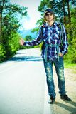 Travel alone. Young man tourist hitchhiking along a road Stock Images