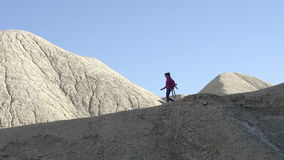 Travel Along the Canyon. Girl with a backpack and gear moves along the slope of the canyon in the evening sun stock footage