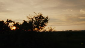 Travel along the scenic countryside at sunset. Silhouettes of trees, the setting sun shines stock video