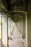 Travel in Angkor Wat. ANGKOR WAT, SIEMPEAP, KHMER REPUBLIC - NOVEMBER 6 : The unidentified man is walking in cloister of Angkor Wat, one of the world heritages royalty free stock photography
