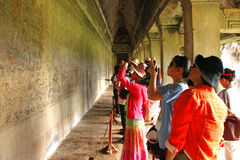 Travel in Angkor Wat. ANGKOR WAT, SIEMPEAP, KHMER REPUBLIC - NOVEMBER 6 : The unidentified people are looking and someone are taking a photograph of carving on stock image