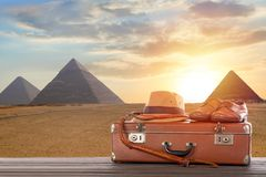 Travel, archeology and adventure concept. Vintage brown suitcase with fedora hat, bullwhip and shoes against Great pyramids in. Giza valley during sunset stock photos