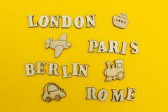 Travel around Europe, the names of cities: `Paris, London, Berlin, Rome` on a yellow background. Wooden figures of an airplane, stock photos