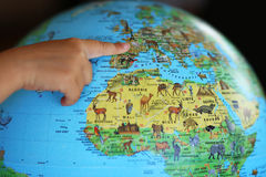 Travel around the word illustration. A child points his finger on a world map stock images