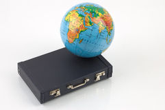 Travel around the world. Little globe and a black suitcase against the white background stock photo