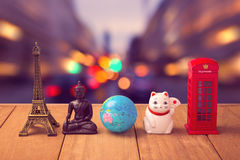 Travel around the world concept. Souvenirs from around the world on wooden table over city bokeh background stock photos