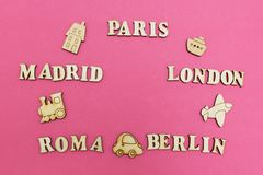 Travel around the world, the names of cities: `Paris, London, Madrid, Berlin, Rome` on a pink background. Wooden figures of an a stock images