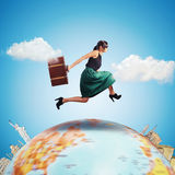 Travel around the world. Woman runs with a suitcase over the world Stock Photos