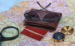 Travel Arrangement. Travel Concept. Travel arrangement of wallet, sun glasses,  two passports, compass and magnifying glass on a map background. Travel concept Stock Photo