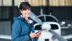Travel and aviation apps. Confident female pilot in the hangar preparing before departure, she is using aviation apps on her tablet and smiling at camera, light Stock Image