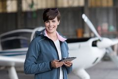 Travel and aviation apps. Confident female pilot in the hangar preparing before departure, she is using aviation apps on her tablet and smiling at camera, light Stock Images