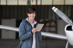 Travel and aviation apps. Confident woman in the hangar preparing before departure, she is using aviation apps on her tablet and smiling at camera, light Royalty Free Stock Photos