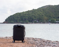 Travel background with a black trolley suitcase Royalty Free Stock Photography