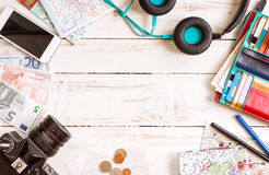 Travel background. Journey planning. Camera, touristic maps, headphones, wallet with credit cards, phone, colorful pens, euro banknotes and coins on the white Royalty Free Stock Photo