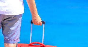 Travel background. Man with suitcase by the sea close-up. Vacation theme stock photos