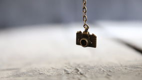 Travel background - toy camera. Bronze toy Camera on a chain over the table. Travel background stock footage