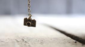 Travel background - toy camera. Bronze toy Camera on a chain over the table. Travel background stock video