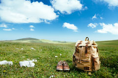 Travel backpack on grass. Travel backpack and shoes on green grass in spring field, blue sky and clouds, idyllic scene Royalty Free Stock Photo