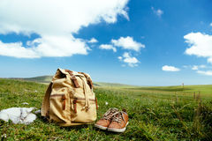 Travel backpack on grass. Travel backpack and shoes on green grass in spring field, blue sky and clouds, idyllic scene Stock Photos
