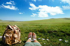 Travel backpack on grass. Travel backpack and traveler's foots on green grass in spring field, blue sky and clouds, idyllic scene Stock Images