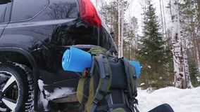 A travel backpack with a mat stands next to the crossover car. Next to the crossover, in a winter snow-covered forest, there is a traveling backpack with a mat stock footage