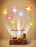 Travel bag with clothes and colorful planes flying out Stock Photo