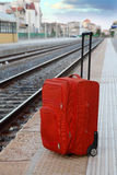 Travel bag stands on platform near railway tracks Royalty Free Stock Image