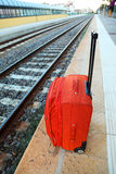 Travel bag stands on platform near railway tracks Stock Image