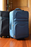 Travel baggages. Two packed baggages in front of a door ready for the next travel Stock Images