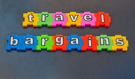Travel bargains. Text ' travel bargains ' in colorful lower case letters in jigsaw style pieces , isolated on a dark gray background Royalty Free Stock Photography