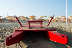 Travel beach Romagna - beach and sea in Rimini with red rescue boat. And orange umbrellas stock image