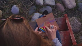 Travel: beautiful girl tourist drawing sunset at. The beach. Close-up shot, slow-motion 60fps, handheld, HD stock video