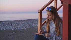 Travel: beautiful girl tourist drawing sunset at. The beach. Medium shot, slow motion 60fps, handheld, HD stock video footage
