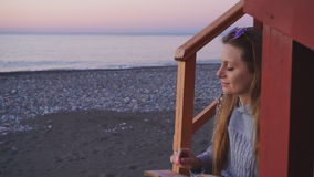 Travel: beautiful girl tourist drawing sunset at. The beach. Medium shot, slow motion 60fps, handheld, HD stock video