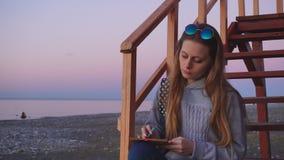 Travel: beautiful girl tourist drawing sunset at. The beach. Medium shot, slow motion 60fps, handheld, HD stock footage