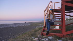 Travel: beautiful girl tourist drawing sunset at. The beach. Wide shot, slow motion 60fps, handheld, HD stock footage