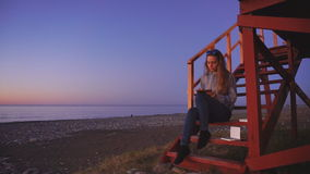 Travel: beautiful girl tourist drawing sunset at. The beach. Wide shot, static, HD stock footage