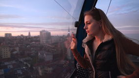 Travel: beautiful young woman tourist looking. Through the glass, making photos with her cellphone in the ropeway cabin at sunset. Medium shot, slow motion 60 stock video