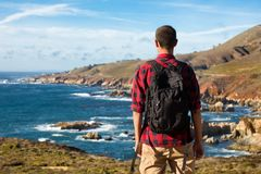 Travel in Big Sur, man Hiker with backpack enjoying view coastline pacific ocean, California, USA royalty free stock images